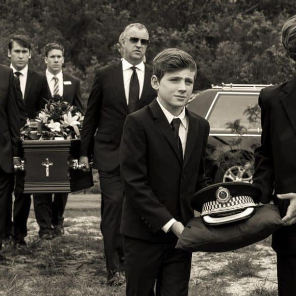 funeral photography - two grandsons carrying their grandfather's police hat