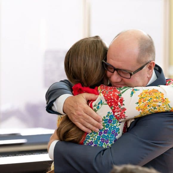 funeral photography - siblings embracing during funeral service