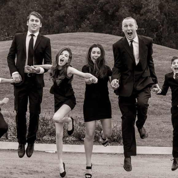 funeral photography - grandchildren leaping at the wake of their grandfather